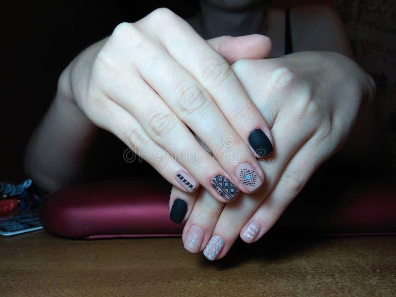 De manicure maakte uitstekend tot haar werk een mooie manicure met een poetsmiddelgel op haar handen en de cliënt is gelukkig stock foto