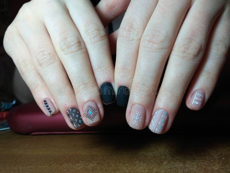 De manicure maakte uitstekend tot haar werk een mooie manicure met een poetsmiddelgel op haar handen en de cliënt is gelukkig stock foto's