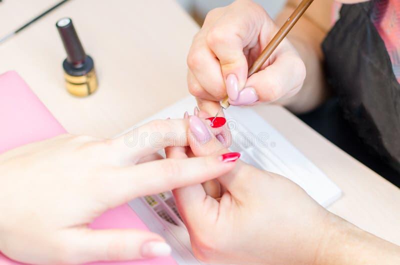 De manicure schildert spijkers met rode lak in de salon stock foto's