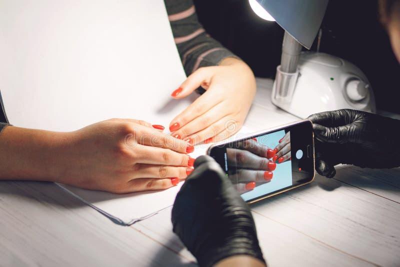 De manicurespecialist in zwarte handschoenen neemt beelden van handen met rode spijkers telefonisch Manicure in schoonheidssalon  royalty-vrije stock foto