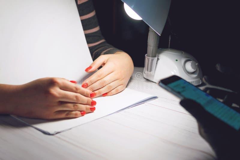 De manicurespecialist in zwarte handschoenen neemt beelden van handen met rode spijkers telefonisch Manicure in schoonheidssalon  royalty-vrije stock afbeelding