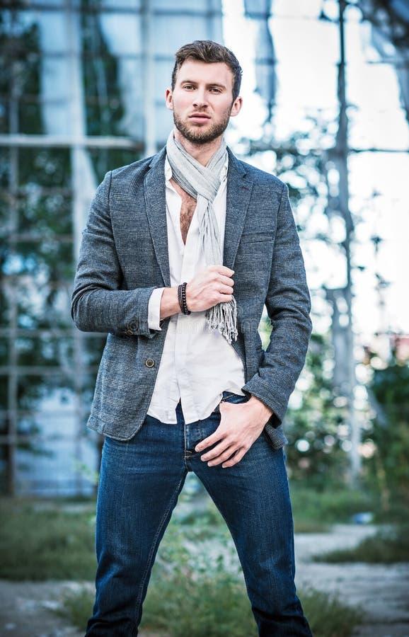 De manier schoot: portret van de knappe jonge mens die jeans, overhemd, jasje en sjaal dragen royalty-vrije stock afbeeldingen