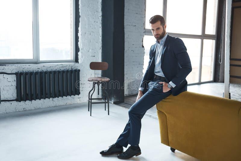 De manier ziet eruit De aantrekkelijke en modieuze zakenman denkt over het werk in het moderne bureau royalty-vrije stock foto's
