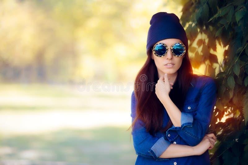 De Maniermeisje van de straatstijl in Denimoverhemd die Blauwe Zonnebril dragen stock afbeelding