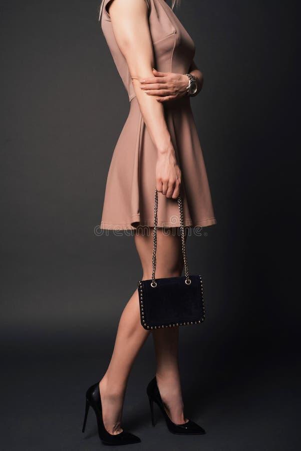 De maniermeisje van de straatstijl, die kledings zwarte schoenen dragen die kleine handtas met details houden stock foto
