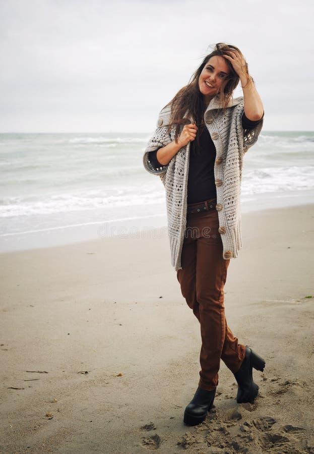 De manierportret van de de herfstlevensstijl van het jonge modieuze hipstervrouw lopen op een overzees strand stock foto's