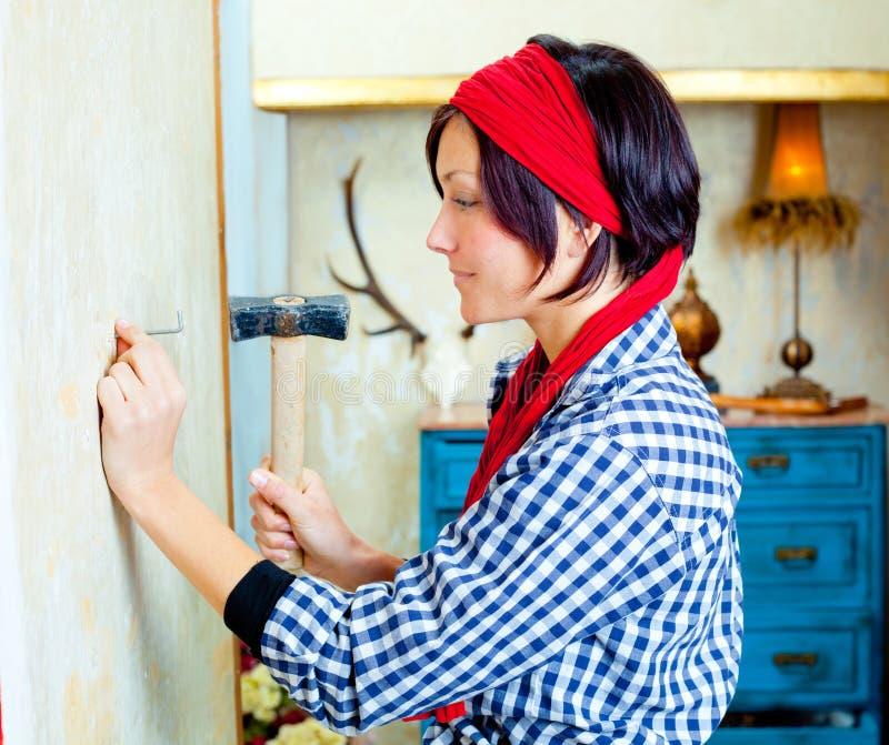 De maniervrouw van Diy met spijker en hamer stock fotografie