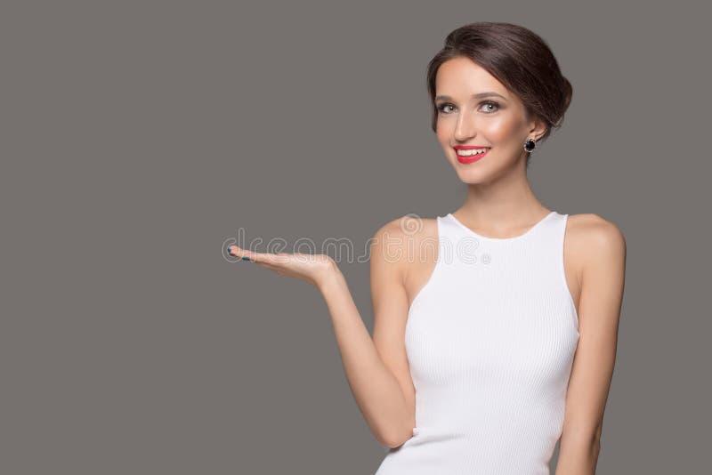 De maniervrouw in witte kleding en mooie glimlach richt aan een lege ruimte stock fotografie