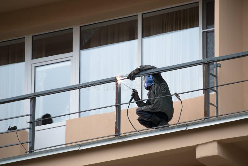 De mannelijke arbeider last metaaltraliewerk op het balkon van het gebouw stock afbeelding