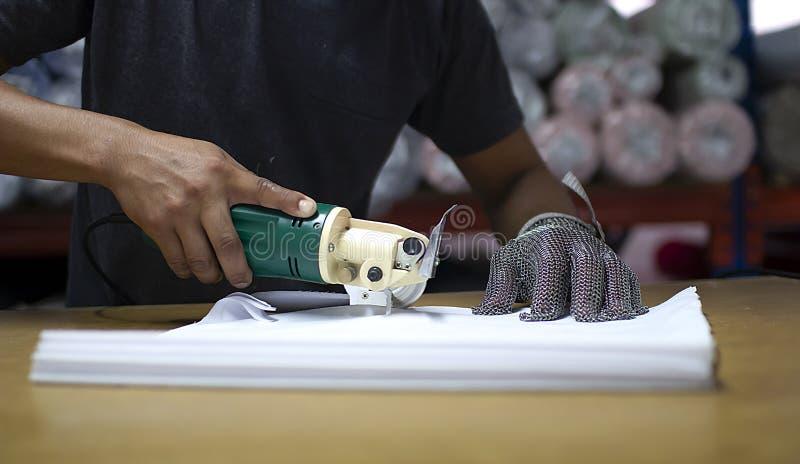 De mannelijke arbeider op een het naaien vervaardiging gebruikt elektrische scherpe stoffenmachine met kettingshandschoen royalty-vrije stock afbeeldingen