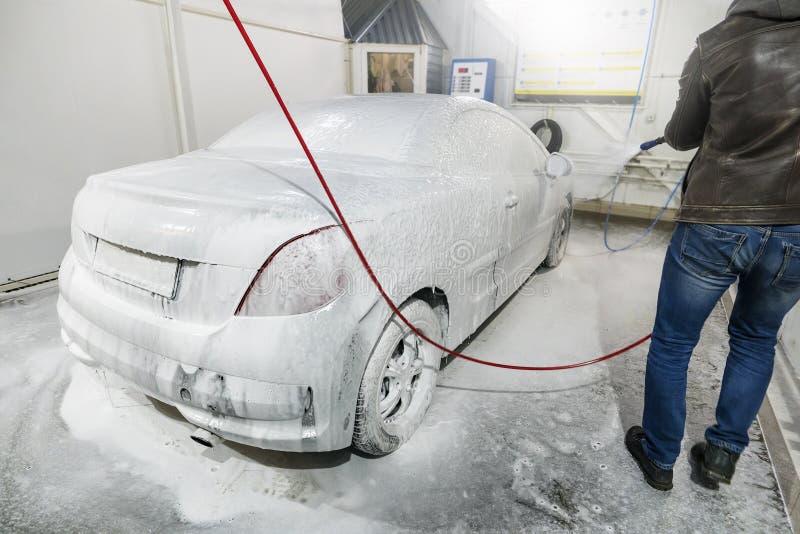 De mannelijke arbeider wast de auto met hoge drukwasmachine Autowasserette met schuim in autowasserettepost Een mens bespuit schu royalty-vrije stock foto