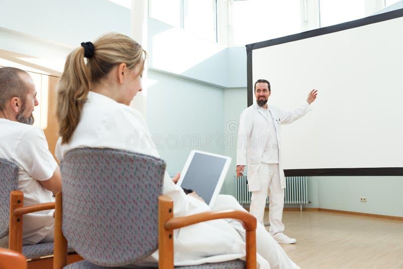 De mannelijke arts doet een lezing stock foto's