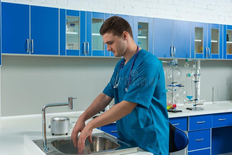 De mannelijke arts in eenvormige was van hem dient moderne laborator in stock fotografie