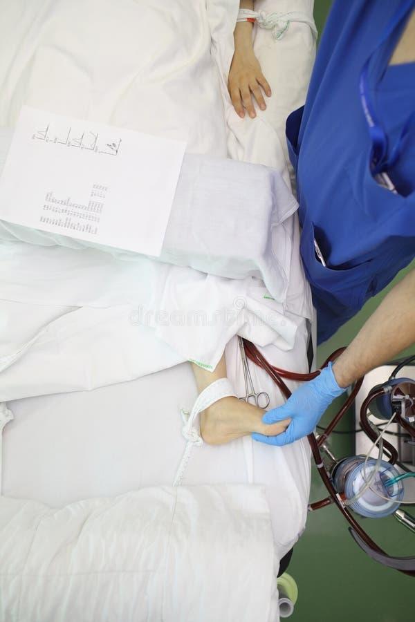 De mannelijke arts palpeert de geduldige voet van ` s tijdens hemodilysis p royalty-vrije stock foto