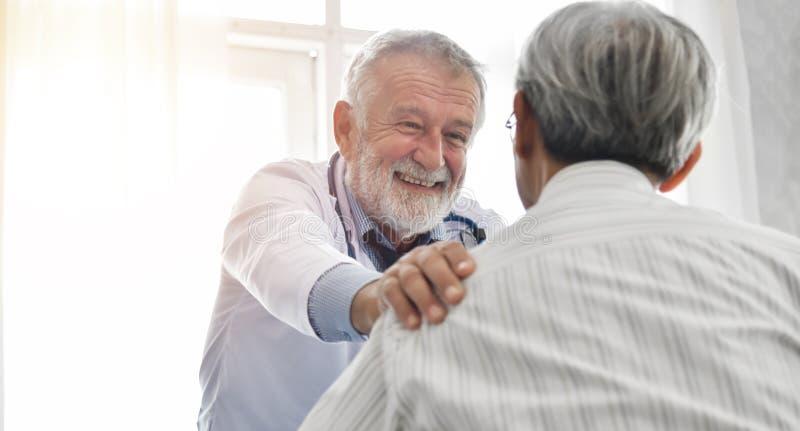 De mannelijke arts troost mannelijke patiënt stock foto's
