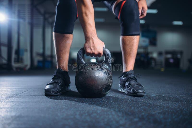 De mannelijke atleet treft voor oefening met kettlebell voorbereidingen stock afbeeldingen