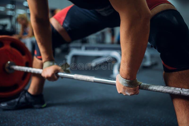 De mannelijke atleet treft voorbereidingen om barbell te trekken stock foto