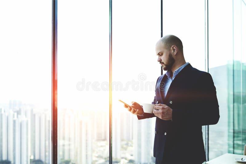 De mannelijke bankier bevindt zich dichtbij de achtergrond van het wolkenkrabbervenster met exemplaarruimte voor uw reclame royalty-vrije stock foto