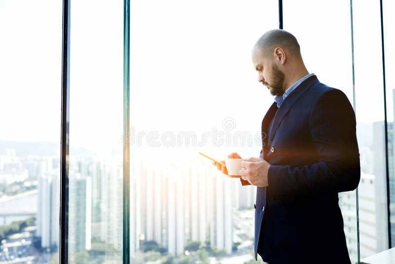 De mannelijke bankier bevindt zich met kop van koffie ter beschikking in bureaubinnenland tegen venster met exemplaarruimte stock fotografie