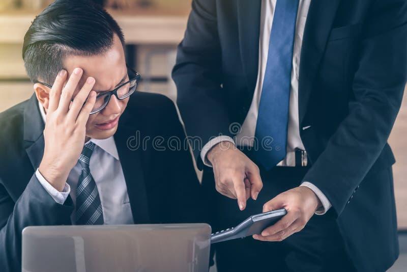 De mannelijke bedrijfsmens wordt beschuldigd door een werkgever die een calculator houdt royalty-vrije stock foto's