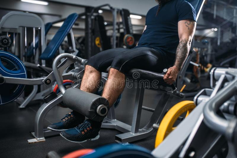 De mannelijke benen van persoonstreinen op oefeningsmachine in gymnastiek royalty-vrije stock foto