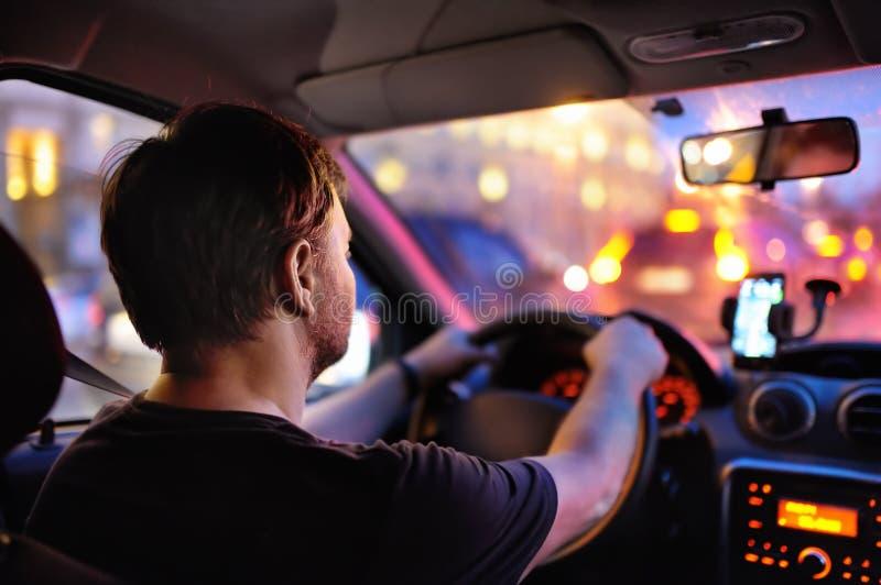 De mannelijke bestuurder berijdt een auto tijdens avondopstopping stock afbeeldingen