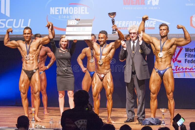 De mannelijke bodybuilders vieren hun kampioenschapsoverwinning met offi stock foto's