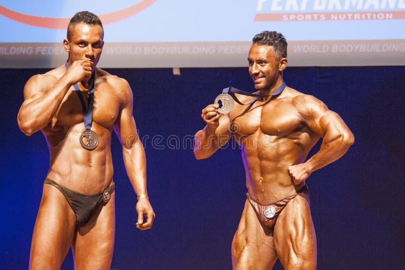 De mannelijke bodybuilders vieren hun kampioenschapsoverwinning op stadium stock afbeelding
