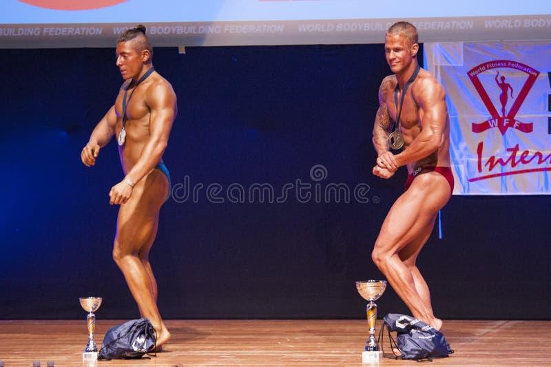 De mannelijke bodybuilders vieren hun kampioenschapsoverwinning op stadium royalty-vrije stock foto