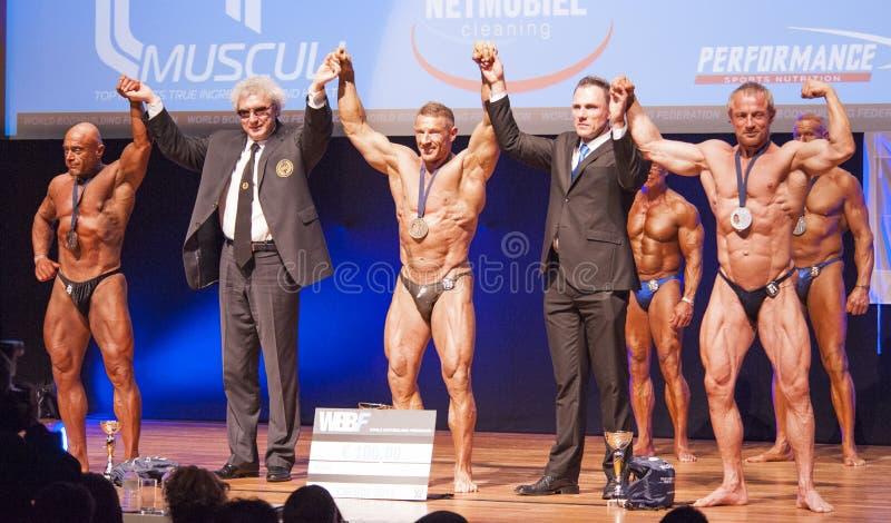 De mannelijke bodybuilders vieren hun kampioenschapsoverwinning op stadium stock fotografie