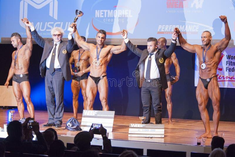 De mannelijke bodybuilders vieren hun kampioenschapsoverwinning op stadium stock foto's