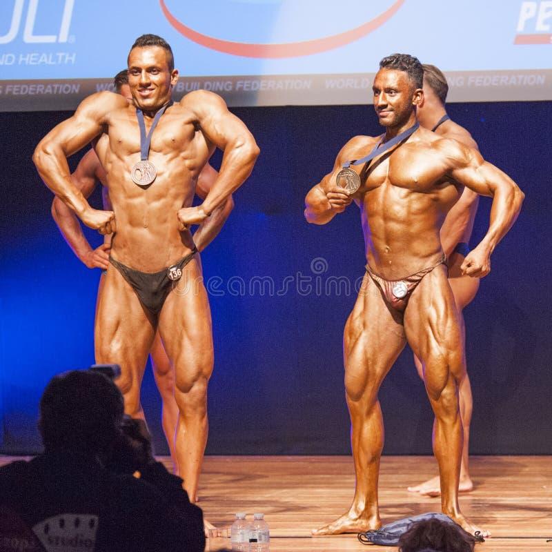 De mannelijke bodybuilders vieren hun kampioenschapsoverwinning op stadium royalty-vrije stock afbeeldingen