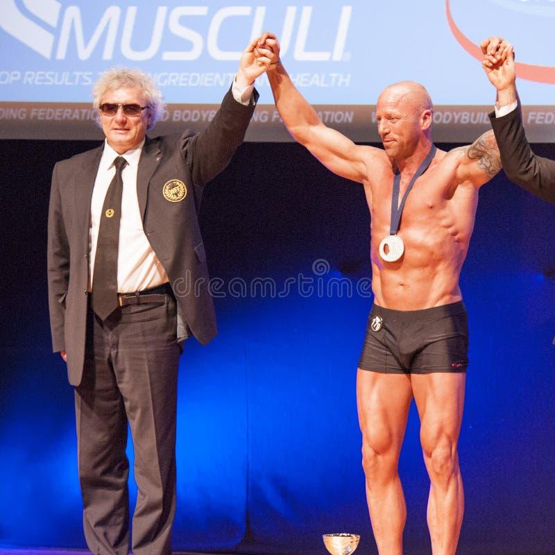 De mannelijke bodybuilders vieren hun kampioenschapsoverwinning op stadium stock afbeeldingen