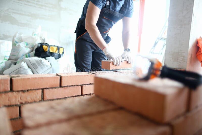 De mannelijke bouwer dient handschoenen het houden in stock foto