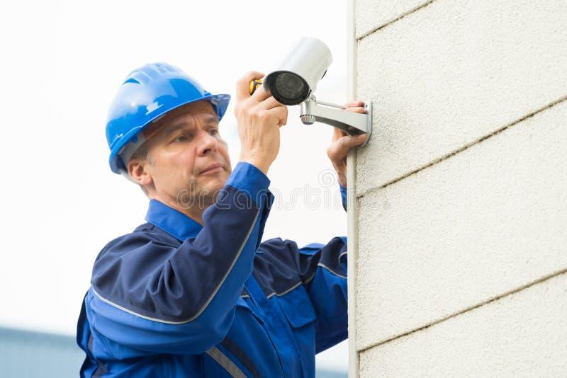 De mannelijke Camera van kabeltelevisie van TechnicusFixing op Muur stock foto's