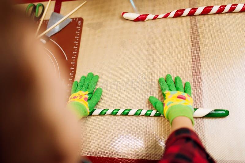 De mannelijke chef-kok dient handschoenen, karamel makend proces in stock foto