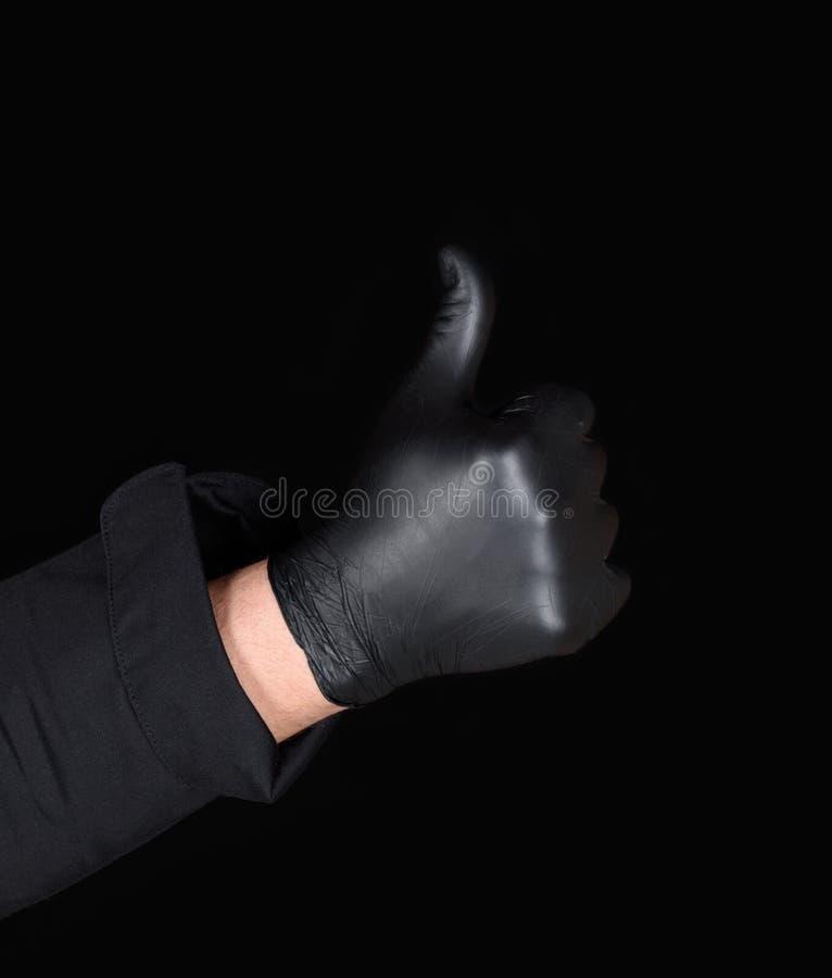 De mannelijke chef-kok dient zwarte latexhandschoenen in toont een gebaar van goedkeuring royalty-vrije stock afbeelding