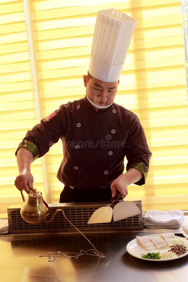 De mannelijke chef-kok giet olie royalty-vrije stock afbeeldingen