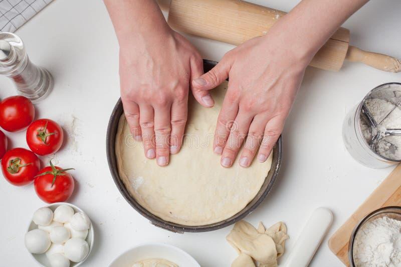 De mannelijke chef-kok zet het ontwikkelde deeg in een pizzavorm Op de witte lijst zijn de tomaten, de mozarellaballen, de olijfo royalty-vrije stock foto's