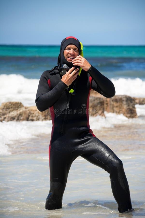 De mannelijke duiker met het duiken kostuum snorkelt maskervinnen op het strand stock foto's