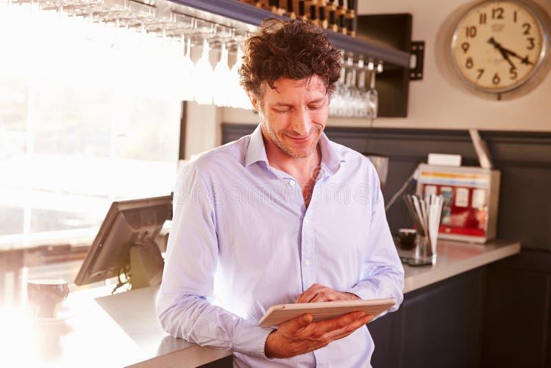 De mannelijke eigenaar die van de restauranteigenaar digitale tablet gebruiken stock afbeelding
