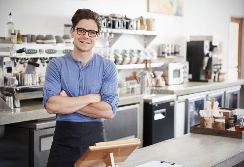 De mannelijke eigenaar van de koffiewinkel achter de teller, gekruiste wapens stock fotografie