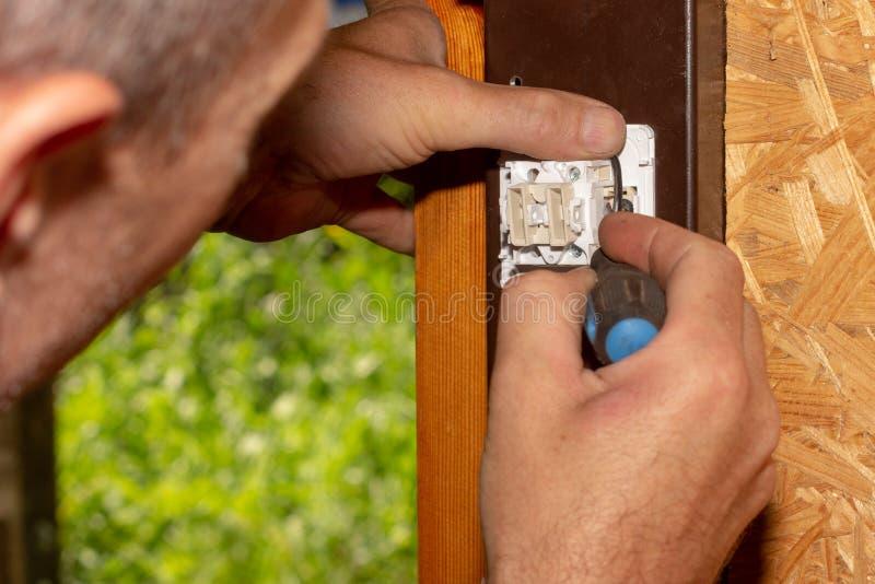 De mannelijke elektricien zet een schakelaar op om elektrische verlichting aan te zetten stock afbeeldingen