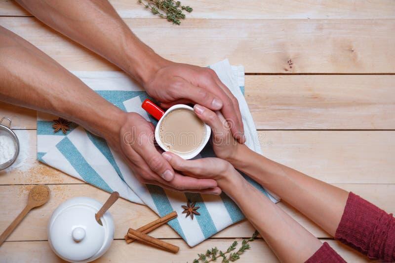De mannelijke en vrouwelijke handen houden een kop tussen hen stock afbeelding