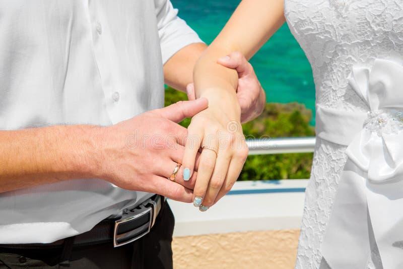 De mannelijke en vrouwelijke handen met trouwringen onder de boog verfraaien royalty-vrije stock fotografie