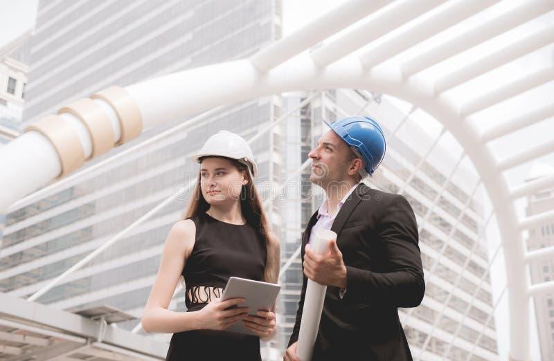 De mannelijke en vrouwelijke industriële ingenieur een tablet en blauwdrukken houden die werkend en op bouwterrein bespreken, sta royalty-vrije stock afbeeldingen