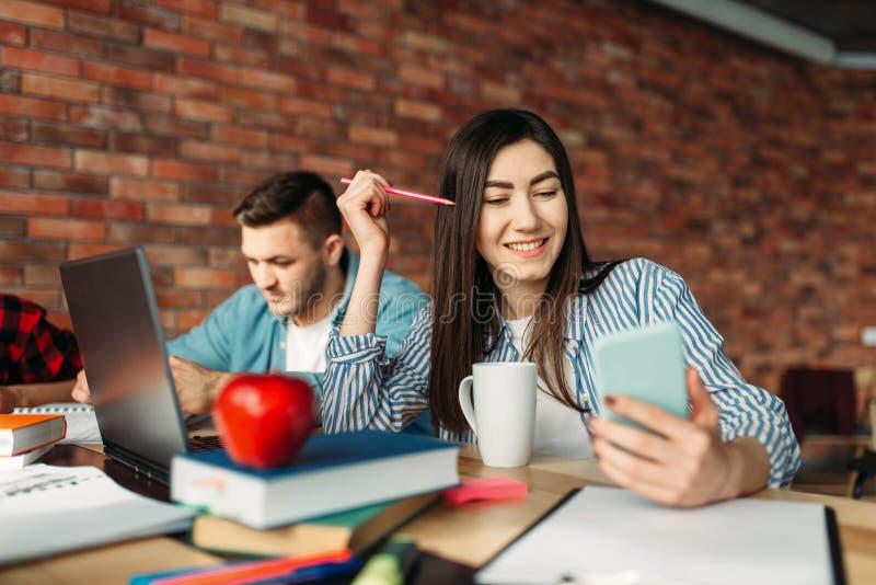 De mannelijke en vrouwelijke studenten treft voor examens voorbereidingen stock foto