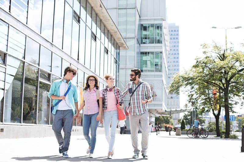 De mannelijke en vrouwelijke vrienden die van gemiddelde lengte op stadsstraat lopen stock foto