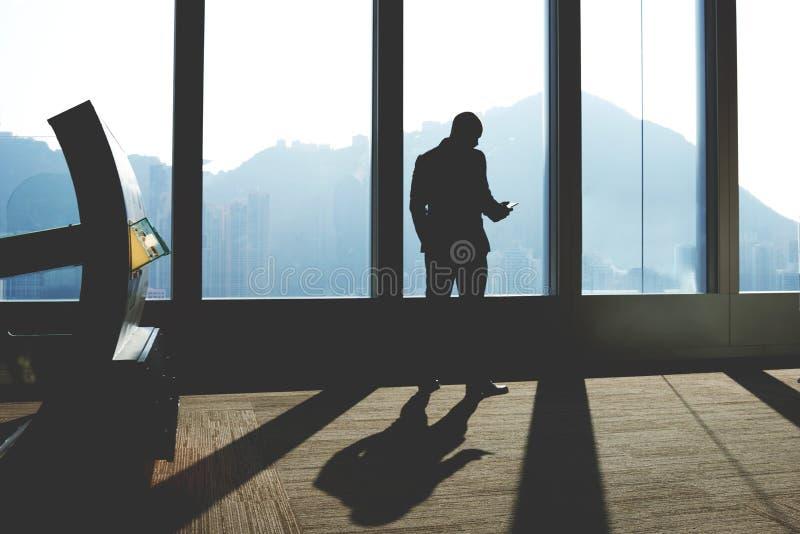 De mannelijke financier leest financieel nieuws in netwerk op mobiele telefoon royalty-vrije stock afbeeldingen