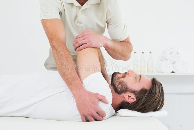 De mannelijke fysiotherapeut die jong uitrekken bemant hand royalty-vrije stock fotografie